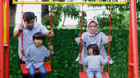 malajské : Attractive muslim family with two children playing on the swing at playground. Shot in 4k resolution Dostupné videozáznamy