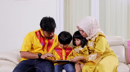 sourozenci : Attractive muslim family with two children using a digital tablet while sitting on the sofa in the living room at home. Shot in 4k resolution