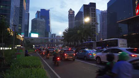 preso : JAKARTA, Indonesia - February 11, 2019: Cars and motorcycle stacked on traffic jam with skyscrapers background at dusk time in Jakarta, Indonesia. Shot in 4k resolution