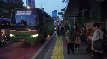 station de bus : JAKARTA, Indonesia - February 11, 2019: Crowded people on bus stop with traffic jam background on rush hour in Jakarta, Indonesia. Shot in 4k resolution Vidéos Libres De Droits