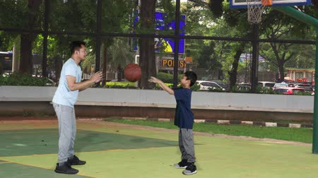 abroncs : Young man teaching his son how to pass a basketball at the outdoors basketball court. Shot in 4k resolution