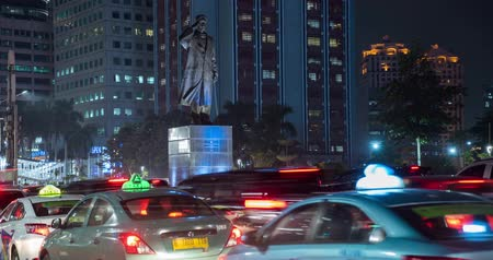 sudirman : JAKARTA, Indonesia - February 11, 2019: Time lapse footage of traffic jam with crowded vehicles and Sudirman statue background at night on Sudirman street in Jakarta. Shot in 4k resolution