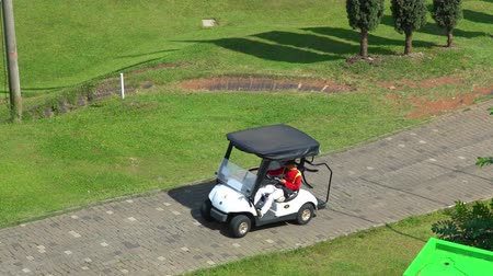 game drive : BANDUNG, Indonesia - February 13, 2019: Aerial view of man driving a golf cart at Heritage Dago Golf Course. Shot in 4k resolution