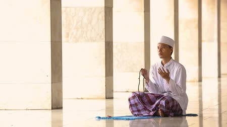 Аллах : Religious muslim man praying inside the Istiqlal Mosque in Jakarta, Indonesia.