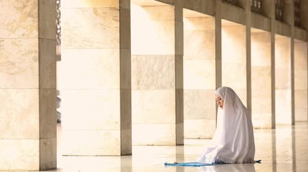 mesquita : Muslim woman praying inside the Istiqlal Mosque in Jakarta, Indonesia.