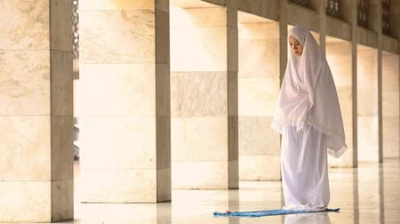 malajské : Religious muslim woman praying inside the Istiqlal Mosque in Jakarta, Indonesia.