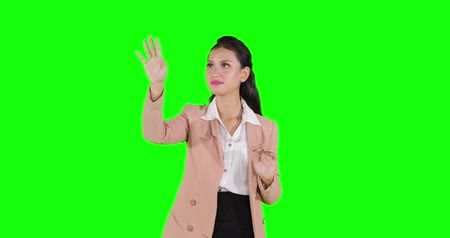 стоять : Attractive business woman pressing virtual screen. Shot in 4k resolution with green screen background