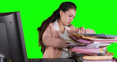 polinésia : Frustrated business woman finding a document on a pile of documents at the table. Shot in 4k resolution with green screen background