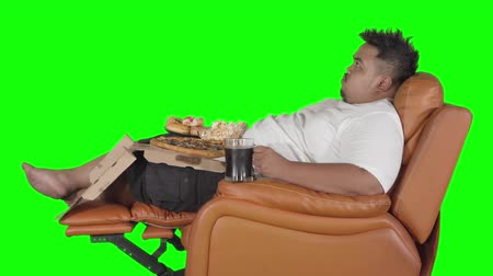 voracious : Fat man eating junk foods and drink a glass of cola while sitting on the sofa. Shot in 4k resolution with green screen background