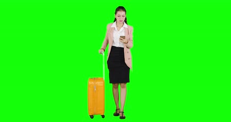 fulllength : Worried business woman making a phone call while holding her luggage. Shot in 4k resolution with green screen background