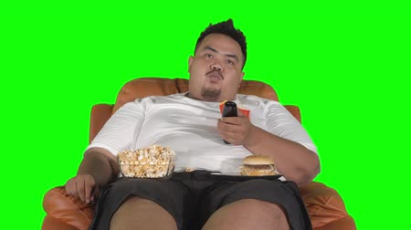 ganancioso : Young overweight man watching TV while eating popcorn and burger on the sofa. Shot in 4k resolution with green screen background Vídeos