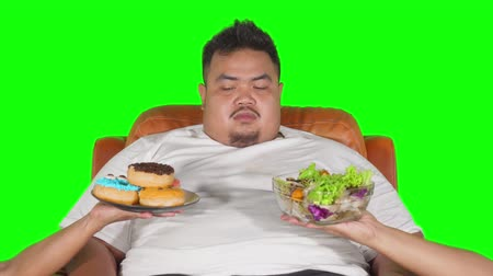 doubt : Confused overweight man choosing donuts or vegetables salad. Shot in 4k resolution with green screen background