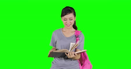 vysoká klíč : Attractive female high school student reading a book and smiling at the camera while standing in studio. Shot in 4k resolution with green screen background