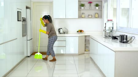 cleaning equipment : Beautiful young woman dancing in the kitchen while sweeping the floor at home. Shot in 4k resolution