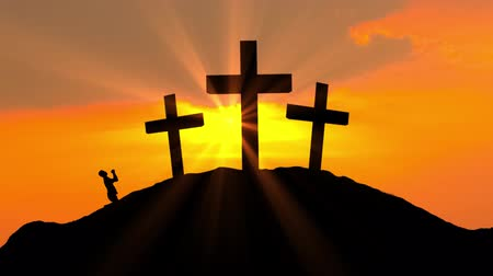 crucifix : Silhouette of religious male christian kneeling and worshiping on three crosses at dusk time. Shot in 4k resolution Stock Footage