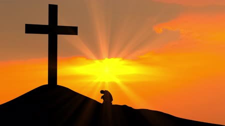 consciência : Silhouette of man kneeling to the cross on the hill at sunset time. Shot in 4k resolution Stock Footage