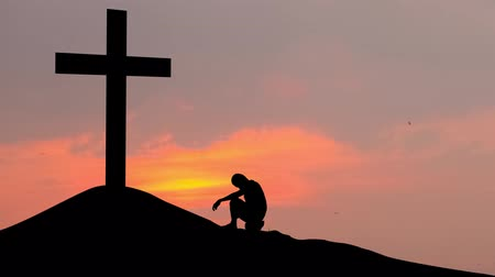 louvor : Silhouette of man making confession to the cross on the hill at sunset time. Shot in 4k resolution