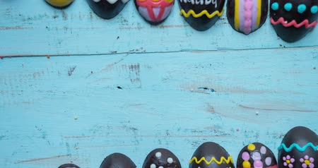 украшать : Stop motion of decorative chocolate easter eggs and happy easter text on wooden table. Shot in 4k resolution