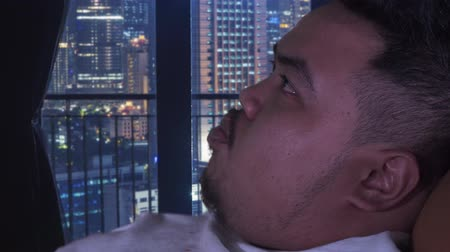 voracious : Closeup of overweight man eating french fries or potatoes while relaxing in apartment. Shot in 4k resolution