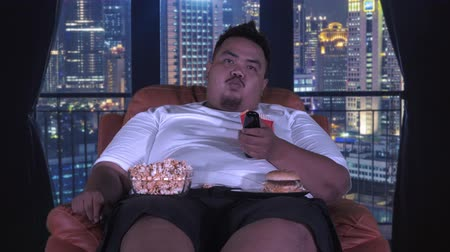 欲 : Overweight man watching TV while sitting on the sofa and eating snacks like popcorn and hamburger in apartment. Shot in 4k resolution 動画素材