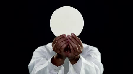 communion : Faceless pastor showing a sacramental bread or communion bread on dark background. Shot in 4k resolution Stock Footage