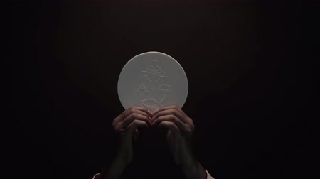 communion : Priest hands raising a communion bread on dark background. Shot in 4k resolution Stock Footage