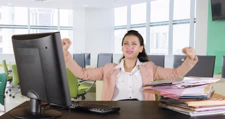 polinésia : Tired young business woman working with computer and taking a break while stretching her arms in office room. Shot in 4k resolution Stock Footage