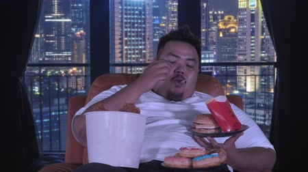 voracious : Overweight man eats junk foods greedily while sitting on the sofa in apartment. Shot in 4k resolution