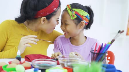 indonesian : Cheerful woman and her daughter painting easter eggs with paintbrush and dyes on the table at home. Shot in 4k resolution