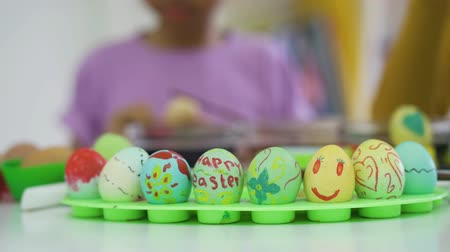 da colorare : Decorative easter eggs and blurred little girl painting easter eggs on the background. Shot in 4k resolution
