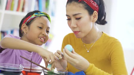 barvivo : Happy young woman and her daughter painting easter eggs with dyes on the table at home. Shot in 4k resolution