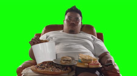 rosquinhas : Greedy overweight man watching TV while eating fried chicken, donuts, burger, and pizza on the sofa. Shot in 4k resolution with green screen background Stock Footage