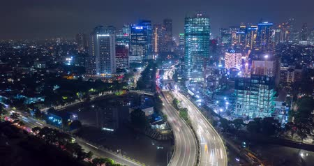 forwards : JAKARTA, Indonesia - March 06, 2019: Beautiful aerial hyperlapse of night traffic on the highway and skyscrapers in business district. Shot in 4k resolution from a drone flying forwards