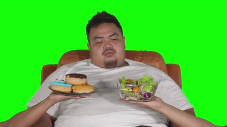 doubt : Overweight man looks confused to choose donuts or vegetables salad. Shot in 4k resolution with green screen background