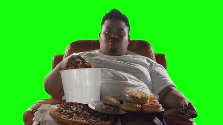 voracious : Greedy obese man watching TV while enjoying junk foods like fried chicken, donuts, burger, and pizza. Shot in 4k resolution with green screen background