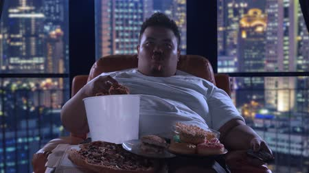 жадный : Bad habit concept. Greedy obese man eating junk foods while watching TV and sitting on the sofa at night in apartment. Shot in 4k resolution