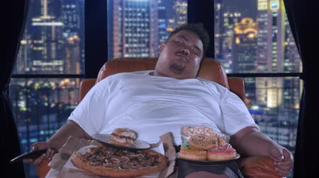 ganancioso : Bad habit concept. Gorged obese man sleeping on the sofa with junk foods after watching TV in his apartment. Shot in 4k resolution