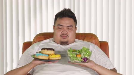 rejeitar : Unhealthy lifestyle concept. Overweight man choosing a plate of donuts and refuse a bowl of vegetable salad. Shot in 4k resolution
