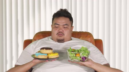 rejeitar : Healthy lifestyle concept. Overweight man choosing a bowl of salad and refuse a plate of donuts. Shot in 4k resolution