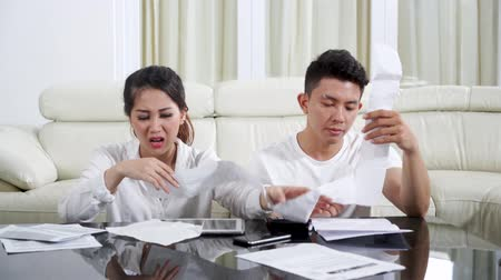 wasteful : Wasteful young couple counting their bill and looks stressful in the living room at home. Shot in 4k resolution