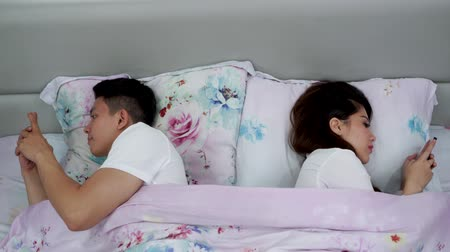 yatma zamanı : Unhappy young couple using mobile phone each others while lying on the bed in bedroom at home. Shot in 4k resolution