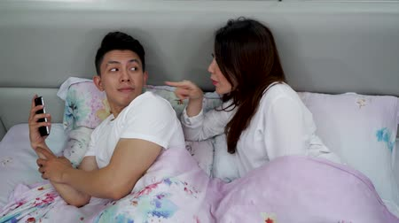 indonesian : Jealous woman spying her husband mobile phone while he is using the mobile phone on bed in bedroom at home. Shot in 4k resolution
