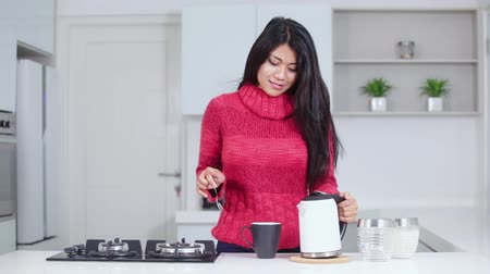 grzejnik : Pretty young woman making hot tea and enjoying it while wearing winter clothes in the kitchen at home. Shot in 4k resolution
