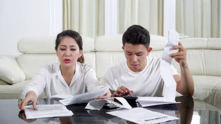 nyugta : Stressful young couple counting their many bill and invoice with a calculator in the living room at home. Shot in 4k resolution