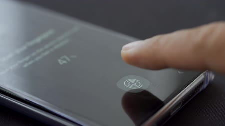 сканер : JAKARTA, Indonesia - March 14, 2019: Human finger scanning fingerprint on modern mobile phone screen. Shot in 4k resolution