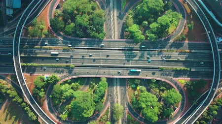 sudirman : Top down view of Semanggi interchange with fast traffic on the morning at weekend in Jakarta downtown, Indonesia. Shot in 4k resolution from a drone flying forwards Stock Footage