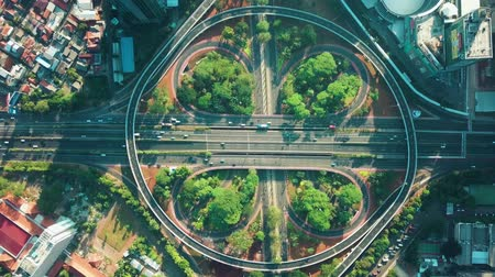 митрополит : JAKARTA, Indonesia - March 14, 2019: Top down view of Simpang Susun Semanggi highway from a drone flying down on the morning. Shot in 4k resolution Стоковые видеозаписи