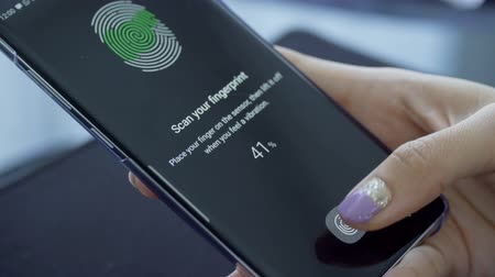 odemknout : JAKARTA, Indonesia - March 14, 2019: Female finger scanning fingerprint on the Samsung Galaxy S10 sensor screen to secure the smartphone. Shot in 4k resolution