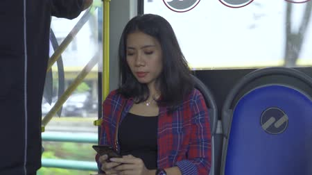 inside bus : JAKARTA, Indonesia - March 21, 2019: Attractive young woman using a smartphone while sitting in the bus. Shot in 4k resolution