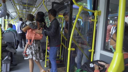 inside bus : JAKARTA, Indonesia - March 21, 2019: Crowded passengers taking modern Transjakarta bus from bus stop. Shot in 4k resolution